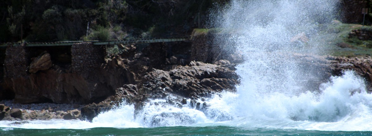 Waves breaking against the rocks at the entrance to the lagoon from the Knysna Heads
